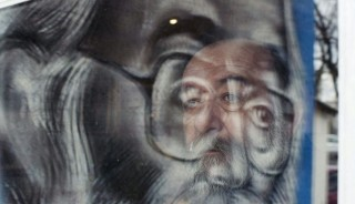 """A man is reflected on a portrait of former Bosnian Serb leader Radovan Karadzic, at a local bar on the outskirts of Belgrade on March 24, 2016. Former Bosnian Serb leader Radovan Karadzic was found guilty today of genocide by UN war crimes judges and sentenced to 40 years in jail over the worst atrocities on European soil since World War II. Karadzic was also found guilty of nine other charges including murder and persecution, but in what will be a blow to thousands of victims, the court in The Hague said it did not have enough evidence to prove """"beyond reasonable doubt"""" that genocide had been committed in seven Bosnian towns and villages during the 1992-1995 war.   / AFP / NEMANJA PANCIC / Serbia OUT"""