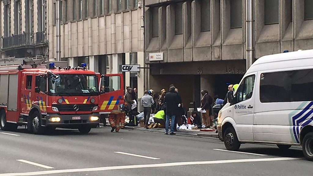 """Emergency services take care of wounded people outside the Maalbeek - Maelbeek metro station in Brussels on March 22, 2016 after a blast at this station located near the EU institutions.Belgian firefighters said at least 21 people had died after """"enormous"""" blasts rocked Brussels airport and a city metro station today, as Belgium raised its terror threat to the maximum level. / AFP / Marija IVONINAITE"""