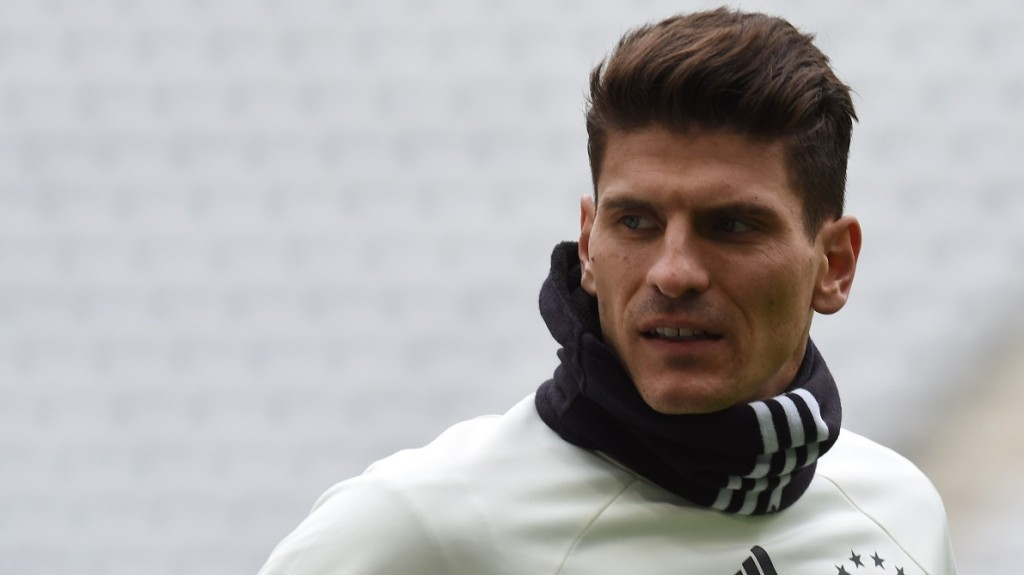 German striker Mario Gomez runs during the final team training session on the eve of the friendly football match Germany vs Italy in Muinch, southern Germany, on March 28, 2016.  / AFP / CHRISTOF STACHE