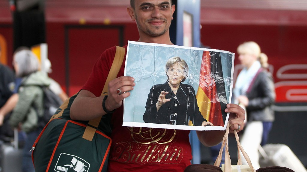 MUNICH, GERMANY - SEPTEMBER 05:  A migrant holds up a poster showing German Chancellor Angela Merkel after his arrival from Austria at Munich Hauptbahnhof main railway station on September 5, 2015 in Munich, Germany. Thousands of migrants are traveling to Germany following an arduous ordeal in Hungary that resulted in thousands walking on foot and then being bussed by Hungarian authorities from Budapest to the Austrian-Hungarian border.  (Photo by Alexandra Beier/Getty Images)