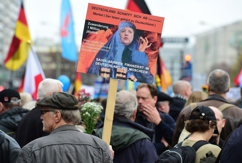 A supporter of the right-wing populist Alternative for Germany (AfD) party displays a placard showing German Chancellor Angela Merkel dressed in a Burqa during a demonstration against the German government's asylum policy organized by the AfD party in Berlin on November 7, 2015. Thousands of protesters marched through the streets of the capital asking for the ouster of German Chancellor Angela Merkel and a curb on the number of asylum-seekers entering Germany. AFP PHOTO / JOHN MACDOUGALL / AFP / JOHN MACDOUGALL