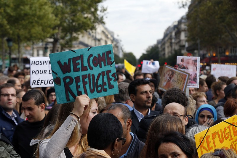 """A person holds a placard reading """"Welcome refugees"""" during a demonstration in support of migrants at the Place de la Republique (Republic square) in Paris on September 5, 2015. Germany and France have agreed that the European Union, facing an unprecedented influx of migrants, should impose binding quotas on the numbers member states take in, German Chancellor Angela Merkel said on September 3, 2015. AFP PHOTO / FRANCOIS GUILLOT / AFP / FRANCOIS GUILLOT"""