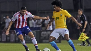 Brazil's Willian (R) vies for the ball with Paraguay's Nestor Ortigoza  during their Russia 2018 FIFA World Cup South American Qualifiers' football match in Asuncion, on March 29, 2016.   AFP PHOTO / PABLO BURGOS / AFP / PABLO BURGOS