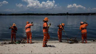 City cleaners collect floated debris on a beach at Guanabara bay in Rio de Janeiro, Brazil on December 26, 2015. The bay, where the nautical sports of Rio 2016 Olympic Games will take place, receives sewage directly from the city system.  AFP PHOTO / YASUYOSHI CHIBA / AFP / YASUYOSHI CHIBA