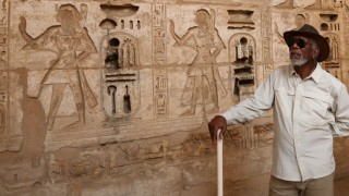 LUXOR, EGYPT - Morgan Freeman stands in front of a wall of hieroglyphs at the mortuary temple of Rameses III in Luxor, Egypt.(photo credit:  National Geographic Channels/Seth Nejame)