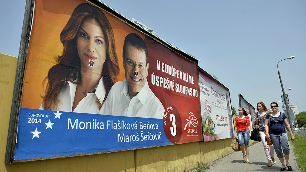 Women walk past a billboard with posters of European Parliament election candidates on May 23, 2014 in Bratislava. European Parliament elections in Slovakia will be held on May 24th. AFP PHOTO/SAMUEL KUBANI / AFP / SAMUEL KUBANI