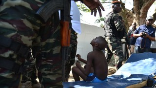 """A wounded child is surrouned by Ivorian security forces after heavily armed gunmen opened fire on March 13, 2016 at a hotel in the Ivory Coast beach resort of Grand-Bassam.At least five people were killed on March 13 when heavily-armed gunmen opened fire in the Ivory Coast resort town of Grand-Bassam, leaving bodies strewn on the beach. """"At the moment there are five dead,"""" a military source said on condition of anonymity after the assault in the resort popular with Westerners. / AFP / SIA-KAMBOU"""