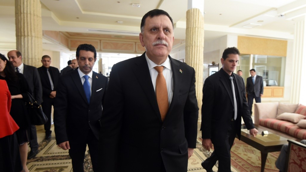 Libya's unity government's Prime Minister-designate, Fayez al-Sarraj (C) arrives for the 8th ministerial meeting of Libya's neighbouring countries on March 22, 2016 in Tunis.  Foreign ministers of neighbouring countries of conflict-wracked Libya are expected to meet together with Arab League chief and UN and EU officials. / AFP / FETHI BELAID