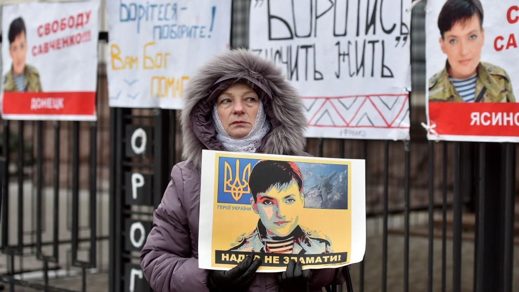 A woman holds a portrait of Ukrainian military pilot Nadiya Savchenko during a demonstration in front of the Russian embassy in Kiev on March 22, 2016. A Russian court on March 22, 2016 sentenced Ukrainian pilot Nadiya Savchenko to 22 years in prison over the killing of two Russian journalists in a ruling set to fuel Moscow's feud with Kiev and the West.   / AFP PHOTO / GENYA SAVILOV