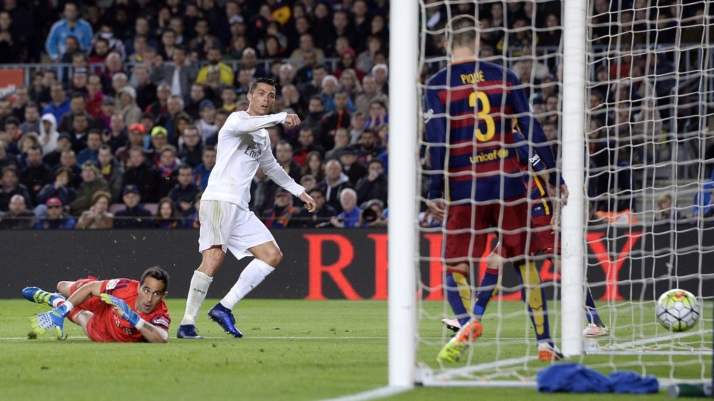 """Real Madrid's Portuguese forward Cristiano Ronaldo (L) looks at the ball after scoring a goal during the Spanish league """"Clasico"""" football match FC Barcelona vs Real Madrid CF at the Camp Nou stadium in Barcelona on April 2, 2016. / AFP / JOSEP LAGO"""
