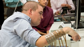 """In this handout picture obtained from the journal """"Nature"""" on April 13, 2016 shows Ian Burkhart, 24, who was paralyzed from the shoulders down after a diving accident in 2010, undertaking tasks after regaining the use of his hand through the use of neural bypass technology at the Ohio State University Wexner Medical Center.   Six years after a diving accident left him paralysed, Ian Burkhart can use his right hand, controlled by his mind and aided by computer software, to stir his own coffee, a groundbreaking trial reported on April 13, 2016. The feat was made possible with a pea-sized chip in the 24-year-old's head to decypher his brain signals and rerouting them to the finger, hand and wrist muscles -- bypassing the damaged spinal cord.The muscles are stimulated by an electrode sleeve worn on the right forearm, with which Burkhart can now also swipe a credit card, grasp a container and pour from it, and play the cords of a guitar video game. / AFP PHOTO / NATURE PUBLISHING GROUP AND AFP PHOTO / Handout / RESTRICTED TO EDITORIAL USE - MANDATORY CREDIT """"AFP PHOTO / Ohio State University Wexner Medical Center/ Batelle"""" - NO MARKETING NO ADVERTISING CAMPAIGNS - DISTRIBUTED AS A SERVICE TO CLIENTS"""