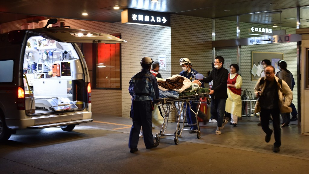 A patient is evacuated by emergency staff from an hospital in Kumamoto City on April 16, 2016, over fears it could collapse as a wave of aftershocks shook the area.  A powerful earthquake hit southern Japan early on April 16, 2016, authorities said, sending panicked residents from their homes and damaging buildings in a region where nerves were already frayed by a swarm of strong shaking. The earthquake hit just over a day after another strong tremor in the same area killed nine people, injured hundreds and toppled buildings.     / AFP PHOTO / KAZUHIRO NOGI