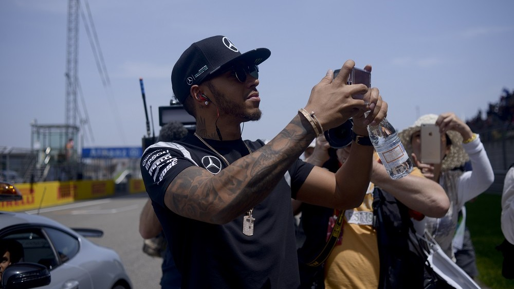 Mercedes AMG Petronas F1 Team's British driver Lewis Hamilton takes a picture as he arrives for the drivers' parade before the start of the Formula One Chinese Grand Prix in Shanghai on April 17, 2016. / AFP PHOTO / WANG ZHAO