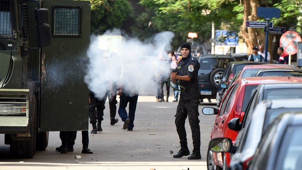 """Egyptian riot police fire tear gas towards protestors as they demonstrate on April 25, 2016 in Cairo against the handing over of two Red Sea islands to Saudi Arabia. Egyptian police fired tear gas at protesters in the Egyptian capital who defied government warnings and held a rally calling for the """"downfall"""" of the regime, quickly scattering them and making arrests.  / AFP PHOTO / MOHAMED EL-SHAHED"""