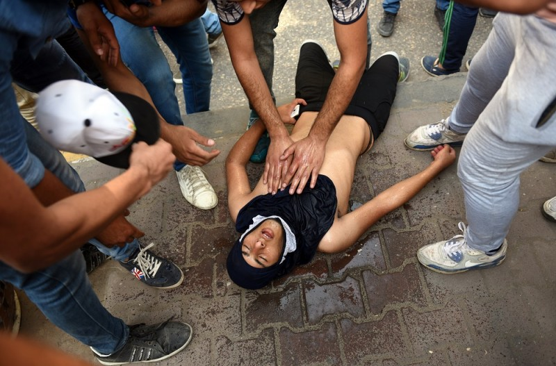 """Egyptian protesters help their comrade suffering from tear gas inhalation  during demonstration in Cairo on April 25, 2016, against the handing over of two Red Sea islands to Saudi Arabia.   Egyptian police fired tear gas at protesters in the Egyptian capital who defied government warnings and held a rally calling for the """"downfall"""" of the regime, quickly scattering them and making arrests.  / AFP PHOTO / MOHAMED EL-SHAHED"""