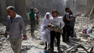 A Syrian family walks amid the rubble of destroyed buildings following a reported airstrike on April 28, 2016 in the Bustan al-Qasr rebel-held district of the northern Syrian city of Aleppo. The death toll from an upsurge of fighting in Syria's second city Aleppo rose despite a plea by the UN envoy for the warring sides to respect a February ceasefire. / AFP PHOTO / Baraa Al-Halabi