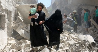 A family walks amid the rubble of destroyed buildings following a reported air strike on the rebel-held neighbourhood of al-Kalasa in the northern Syrian city of Aleppo, on April 28, 2016. The death toll from an upsurge of fighting in Syria's second city Aleppo rose despite a plea by the UN envoy for the warring sides to respect a February ceasefire. / AFP PHOTO / AMEER ALHALBI