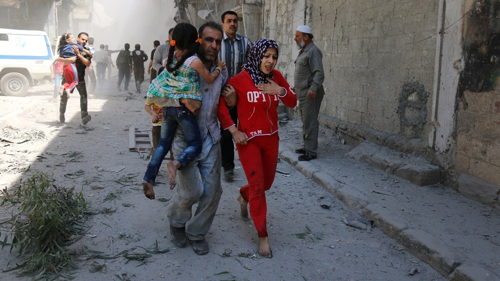 Syrians run for cover amid the rubble of destroyed buildings following a reported air strike on the rebel-held neighbourhood of Al-Qatarji in the northern Syrian city of Aleppo, on April 29, 2016. Fresh bombardment shook Syria's second city Aleppo, severely damaging a local clinic as outrage grows over an earlier air strike that destroyed a hospital. The northern city has been battered by a week of air strikes, rocket fire, and shelling, leaving more than 200 civilians dead across the metropolis. The renewed violence has all but collapsed a fragile ceasefire deal that had brought an unprecedented lull in fighting since February 27.  / AFP PHOTO / AMEER ALHALBI