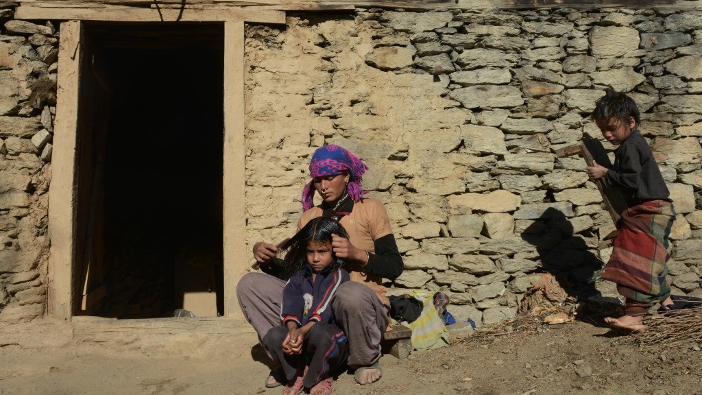 TO GO WITH Nepal-caste-slavery-politics, FEATURE by Ammu Kannampilly In this photograph taken on November 8, 2014,  Nepalese bonded labourer Nani Biswokarma (C) brushes a child's hair outside a house during an interview with AFP in Baraunsi village in Humla district, some 430 kms north-west of Kathmandu. When Nepal's Maoist-led government outlawed bonded labour in 2008 and promised to compensate victims, farmworker Hiralal Pariyar was elated to walk away from a life spent in virtual slavery. But the compensation never came, and soon Pariyar, homeless and penniless, returned to his old landlord, joining thousands of indentured farm labourers who are still waiting for their freedom. AFP PHOTO / PRAKASH MATHEMA / AFP / PRAKASH MATHEMA
