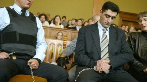 "Accompanied by a police official (L) and an interpretor (R), Azerbaijani army officier Lieutenant Ramil Safarov(C) looks at his watch as the verdict is read 13 April 2006, a convicting him to life imprisonment for hacking to death an Armenian lieutenant while attending a NATO-sponsored training course in Budapest. Judge Andras Vaskuti of the Budapest district court ruled that Ramil Safarov, now 29 and an Azerbaijani army lieutenant, killed Armenian Lieutenant Gurgen Markarian, 26, in ""premeditated, malicious and an unusually cruel"" way by nearly decapitating him with axe while he slept. Safarov will be eligible for parole in 30 years, according to the ruling.     AFP PHOTO / ATTILA KISBENEDEK / AFP PHOTO / ATTILA KISBENEDEK"