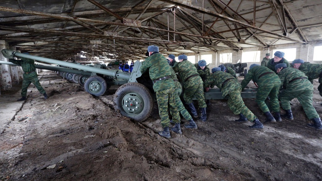 Pro-Russian separatists push an MT-12 Rapira 100-mm anti-tank gun into a hangar in the village of Zelene, Donetsk region, on October 28, 2015. The antitank gun is one of fifteen withdrawn from Donetsk in accordance with the Minsk agreements. Ukraine's warring sides, the pro-Western government and the pro-Moscow rebels, signed their latest in a series of ceasefire agreements on September 1. AFP PHOTO/ ALEKSEY FILIPPOV / AFP PHOTO / ALEKSEY FILIPPOV