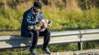 A migrant feeds his baby as refugees and migrants wait to cross the Slovenian-Austrian border from the Slovenian city of Sentilj, on November 3, 2015. Austria's government, facing a record influx of migrants as well as a surge in support for the anti-immigration far-right, moved on November 3, 2015 to tighten asylum rules in the EU country. Austria has seen some 400,000 migrants enter the country since September, most of whom travel onwards to Germany or Scandinavia. AFP PHOTO / RENE GOMOLJ / AFP PHOTO / Rene Gomolj