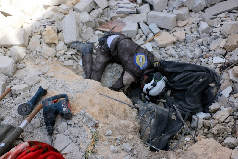 ALEPPO, SYRIA - APRIL 27: Syrians and civil defense team members carry out a search and rescue operation to find the people who trapped under the rubble after the war crafts belonging to the Russian Army carried out airstrikes on a residential area in the Bab Neyrab neighborhood of Aleppo, Syria on April 27, 2016.  Beha el Halebi / Anadolu Agency