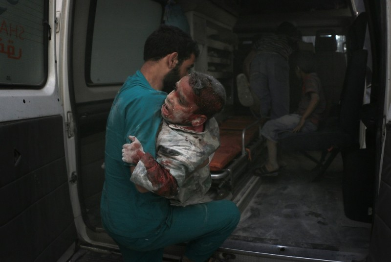 ALEPPO, SYRIA - APRIL 28: (EDITORS NOTE: Image contains graphic content.) A wounded man is taken to hospital by health workers after the war crafts belonging to the Russian army carried out airstrikes on the residential areas in the Sukkeri neighborhood of Aleppo, Syria on April 28, 2016. 