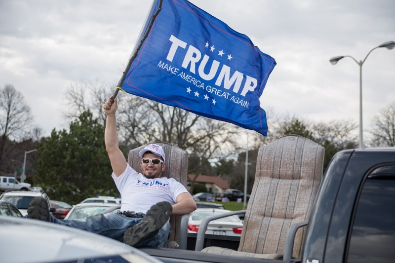 UNITED STATES, West Allis: A Trump supporter waves a blue flag with Donald Trump's political campaign catchphrase on it as Republican presidential candidate Donald Trump speaks to guests during a campaign stop at Nathan Hale High School on April 2, 2016 in West Allis, Wisconsin. Wisconsin voters go to the polls for the state's primary on April 5, 2016. - Jonah White
