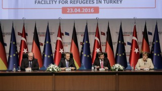 German Chancellor Angela Merkel (R), Turkish Prime Minister Ahmet Davutoglu (2nd R), EU Commission Vice President Frans Timmermans (L) and EU Council President Donald Tusk (2nd L) give a press conference after visiting Nizip refugee camp on the Turkish-Syrian border, in Gaziantep on April 23, 2016.  Merkel is on a high-stakes visit to Turkey aimed at boosting a six-billion-euro (6.7 billion USD) deal plagued by moral and legal concerns to return migrants arriving on Greek shores to Turkey. Ties between Germany and Turkey are strained following President Recep Tayyip Erdogan's warning that the deal would fall through if the EU did not keep up its end of the bargain by allowing visa-free travel for Turkish citizens.  / AFP PHOTO / STR
