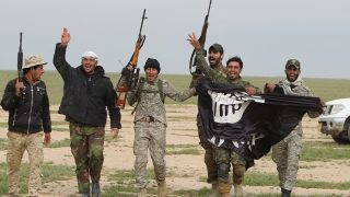 Iraqi Shiite fighters from the Popular Mobilisation units carry an Islamic State (IS) group flag on March 3, 2016, during an operation in the desert of Samarra aimed at retaking areas from IS jihadists. Counter-terrorism forces, soldiers, police and allied paramilitaries are taking part in an operation launched on March 1, which is backed by artillery and both Iraqi and US-led coalition aircraft, aimed at retaking areas north of Baghdad, according to the Joint Operations Command.  / AFP PHOTO / AHMAD AL-RUBAYE