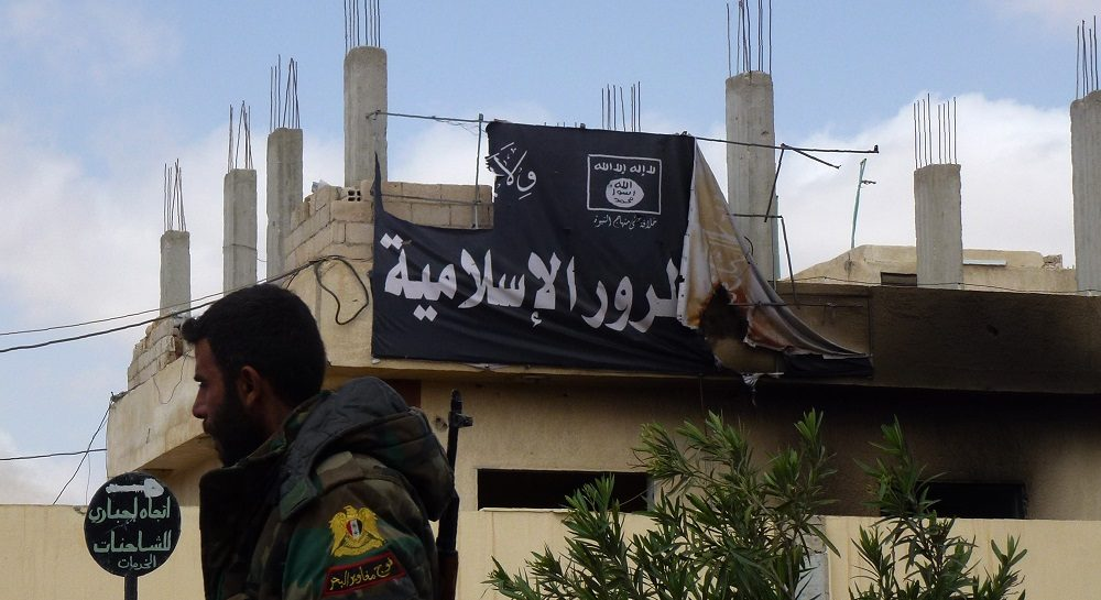 A member of the Syrian government troops walks past a banner bearing Islamic State (IS) group slogans in the damaged streets of the residential neighbourhoods in the modern town adjacent to the ancient Syrian city of Palmyra after they recaptured the UNESCO site from Islamic State (IS) group jihadists on March 27, 2016.  Archaeologists were rushing to the ancient city of Palmyra on March 28, 2016 to assess the damage wreaked by the Islamic State group, after it was ousted by the Syrian army in a bloody battle.  / AFP PHOTO / Maher AL MOUNES