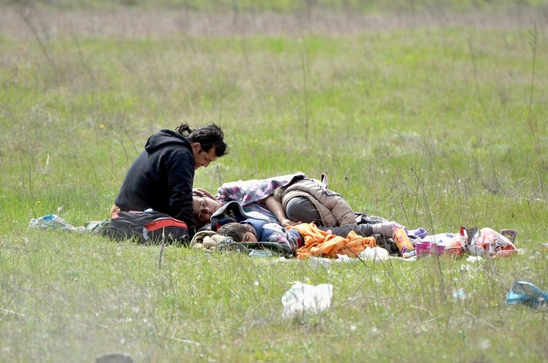 """Migrants lay on the grass and wait to enter the Hungarian transit zone nearby the motorway border crossing of Röszke between Hungary and Serbia on April 1, 2016. Dozens of migrants arrive at the border every day, awaiting admittance into two caged-off Hungarian """"transit zones"""" built into the fence, one at Roszke and another at Tompa 20 kilometres (12 miles) away. / AFP PHOTO / Csaba SEGESVARI / TO GO WITH AFP STORY by PETER MURPHY"""