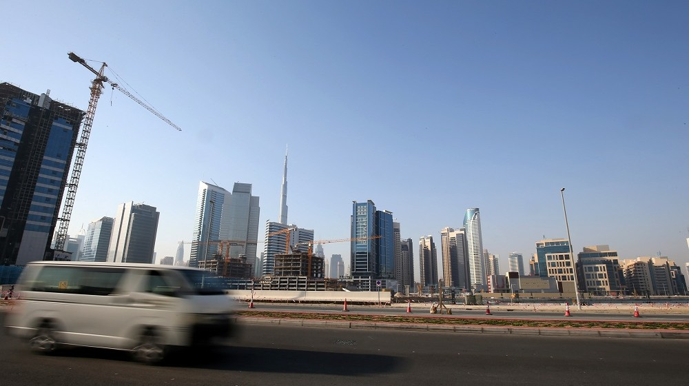 A picture taken on April 27, 2016 shows a car driving past a construction site in Dubai. For more than 10 years Dubai property prices have been on a roller coaster, creating and wiping out fortunes, but recently they appear to have run out of steam.   / AFP PHOTO / MARWAN NAAMANI / TO GO WITH AFP STORY BY ALI KHALIL