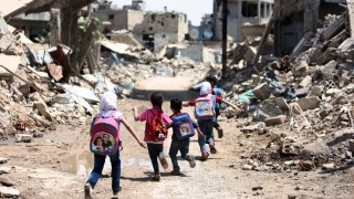Syrian schoolchildren run past heavily damaged buildings in the rebel-held are of Jobar, on the eastern outskirts of the capital Damascus, on April 30, 2016. / AFP PHOTO / AMER ALMOHIBANY