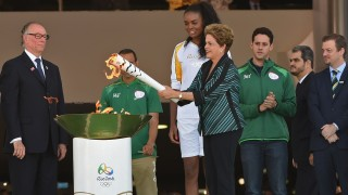 Brazilian President Dilma Rousseff lights the Olympic torch at Planalto Palace in Brasilia following the flame's arrival from Geneva on May 3, 2016, beginning the flame's journey across the country before the start of the 2016 Olympic Games on August 5.  The Olympic flame arrived in Brasilia May 3 aboard a flight from Geneva to embark on a  procession across Brazil culminating in the opening ceremony of the 2016 Games in Rio de Janeiro. The torch will travel to more than 300 towns and cities carried by some 12,000 relay runners before arriving August 5 at the mythic Maracana stadium to kick off the first Olympics in South America. / AFP PHOTO / EVARISTO SA
