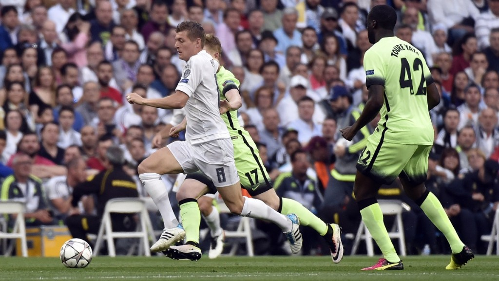 Real Madrid's German midfielder Toni Kroos (L) vies with Manchester City's Ivorian midfielder and captain Yaya Toure (R) and Manchester City's Belgian midfielder Kevin De Bruyne during the Champions League semi-final second leg football match between Real Madrid CF and Manchester City at the Santiago Bernabeu stadium in Madrid on May 4, 2016. / AFP PHOTO / GERARD JULIEN