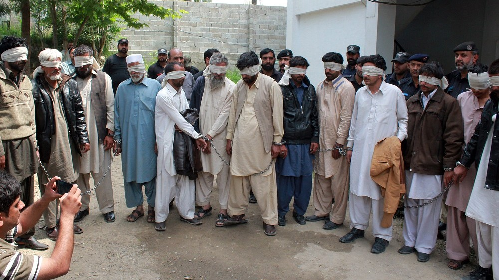 """Pakistani police escort blindfolded suspects accused of killing and setting fire to a woman as they appear at a court in Abbottabad on May 5, 2016.   A Pakistani woman was drugged, strangled and then her body set ablaze because she helped her friend elope, police said May 5, announcing the arrest of 14 people in a twist on the grim practice of """"honour killings"""". / AFP PHOTO / SHAKEEL AHMED"""