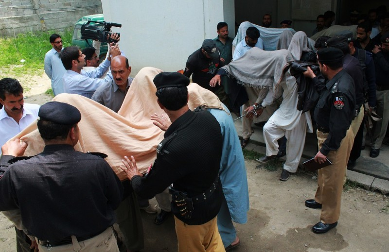 """Pakistani police escort suspects accused of killing and setting fire to a woman as they arrive at a court in Abbottabad on May 5, 2016.   A Pakistani woman was drugged, strangled and then her body set ablaze because she helped her friend elope, police said May 5, announcing the arrest of 14 people in a twist on the grim practice of """"honour killings"""". / AFP PHOTO / SHAKEEL AHMED"""