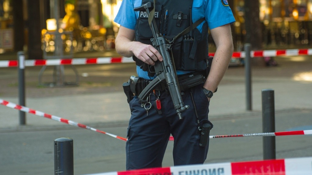 An armed policeman is seen behind a barrier tape at the site of a shooting in the centre of Frankfurt am Main, western Germany, on May 5, 2016. According to the police, several people were injured as shots were fired from a driving car. / AFP PHOTO / dpa / Andreas Arnold / Germany OUT
