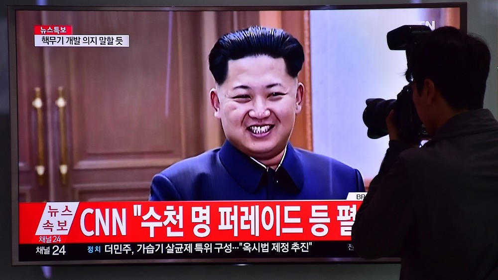 A photographer takes a picture of a television screen showing file footage of North Korean leader Kim Jong-Un, at a railway station in Seoul on May 6, 2016.  North Korea raised the curtain on May 6 on its biggest political show for a generation, aimed at cementing the absolute rule of leader Kim Jong-Un and shadowed by the possibility of an imminent nuclear test. / AFP PHOTO / JUNG YEON-JE