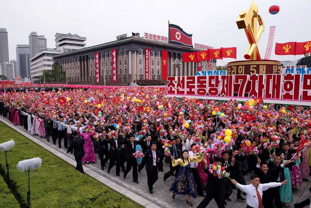 Participants wave flowers towards North Korean leader during a mass parade marking the end of the 7th Workers Party Congress in Kim Il-Sung square in Pyongyang on May 10, 2016.  North Korea kicked off a massive parade in the centre of Pyongyang on May 10 to celebrate a just-concluded ruling party congress that was seen as a formal coronation for supreme leader Kim Jong-Un. / AFP PHOTO / Ed Jones