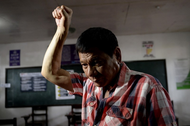 """(FILES) This file photo taken on May 9, 2016 shows Presidential frontrunner and Davao City Mayor Rodrigo Duterte gesturing as he arrive at the voting precint to cast his vote at Daniel Aguinaldo National High School in Davao City, on the southern island of Mindanao.   Philippine president-elect Rodrigo Duterte is planning to visit the Vatican to make a personal apology to the pope for calling him a """"son of a whore"""", the politician's spokesman said on May 12 / AFP PHOTO / NOEL CELIS"""