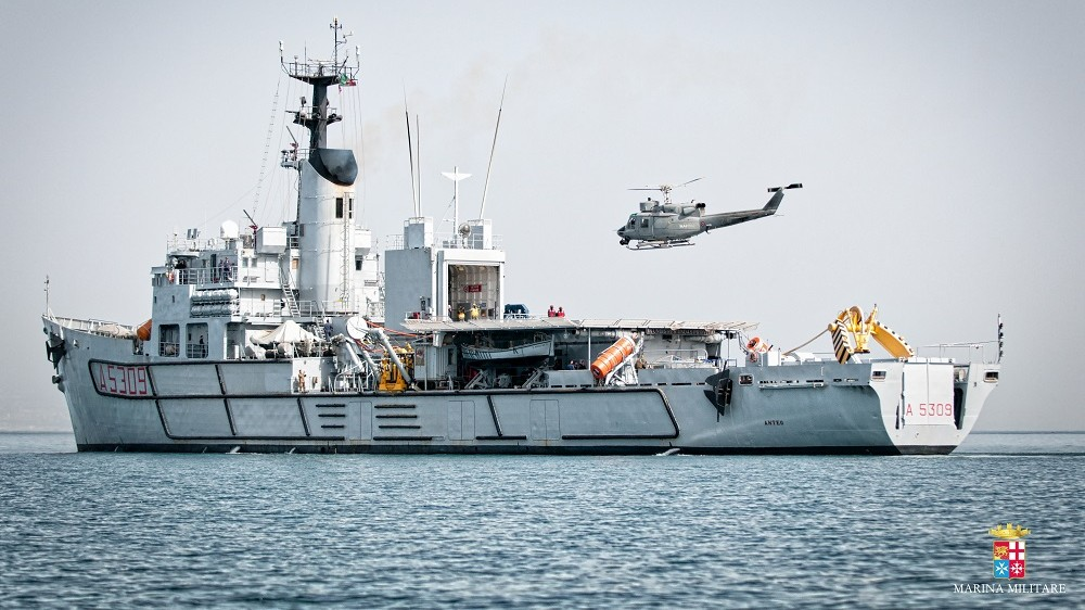 """This handout picture released on May 12, 2016 by the Italian Navy press office, Marina Militare, shows a helicopter and a vessel at the beginning of operations by Italy's navy in charge of the grisly task of raising a corpse-packed trawler from the seabed near Libya, a year after up to 800 migrants perished in the Mediterranean's worst disaster since World War II.  The Italian companies are using a specially designed device with hydraulic arms and underwater cameras to lift the wreck from its resting place, 380 metres (around 1,245 feet) down.   ==RESTRICTED TO EDITORIAL USE - MANDATORY CREDIT """"AFP PHOTO / MARINA MILITARE / HO"""" - NO MARKETING NO ADVERTISING CAMPAIGNS - DISTRIBUTED AS A SERVICE TO CLIENTS== XGTY / AFP PHOTO / MARINA MILITARE / - / RESTRICTED TO EDITORIAL USE - MANDATORY CREDIT """"AFP PHOTO / MARINA MILITARE / HO"""" - NO MARKETING NO ADVERTISING CAMPAIGNS - DISTRIBUTED AS A SERVICE TO CLIENTS"""
