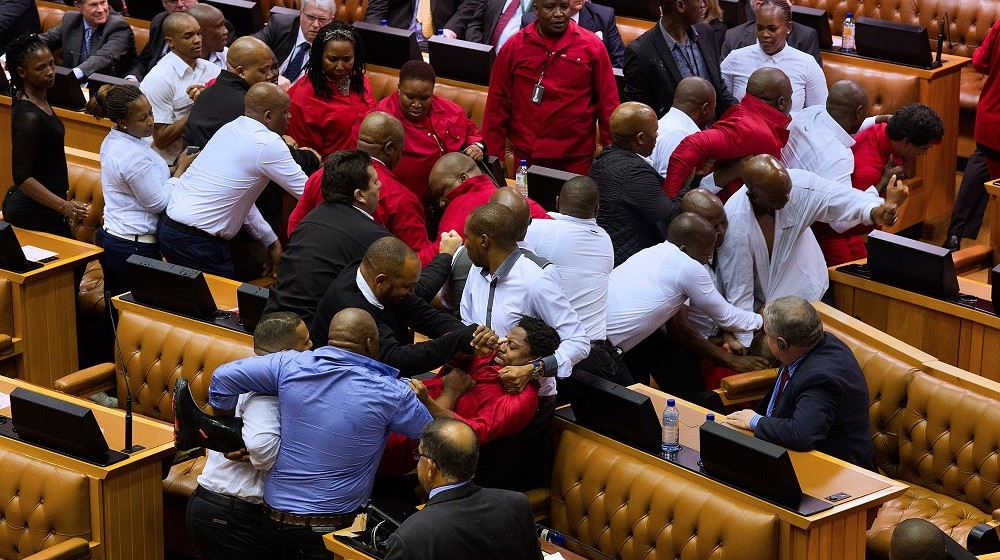 Economic Freedom Fighters (EFF, in red) party members of parliament are physically removed from the South African parliament after repeatedly ignoring the instructions of the Speaker, on May 17, 2016, in Cape Town. A brutal fistfight broke out in the South African parliament on May 17 as security guards ejected opposition lawmakers in an ugly fracas that underlined heightened political tensions over Jacob Zuma's presidency. / AFP PHOTO / RODGER BOSCH