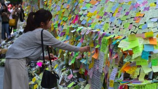 South Koreans leave messages written on post-it notes at an exit of Gangnam subway station, which has been turned into a mini shrine for a 23-year-old woman who was stabbed to death by a stranger the previous night in a nearby public bathroom, in Seoul on May 20, 2016. The brutal murder of a woman in Seoul's upmarket Gangnam district has triggered a public outcry and a debate over what some see as a growing streak of violent misogyny in South Korea. / AFP PHOTO / JUNG YEON-JE