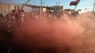 "Supporters of Iraqi cleric Moqtada al-Sadr react to tear gas fired by security forces during clashes after demonstrators broke into Baghdad's fortified ""Green Zone"" on May 20, 2016. Several people were wounded in the process and many others were also hurt outside the walls of the Green Zone, where security forces fired tear gas directly into the crowd to keep the bulk of the protesters at bay.  Security forces also fired live rounds but it was not immediately clear how many people were wounded and what the nature of their injuries was. / AFP PHOTO / AHMAD AL-RUBAYE"
