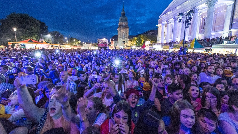 A photo taken on May 26, 2016 in Darmstadt, western Germany shows people enjoying an open air concert during the Schlossgrabenfest music festival.  German police arrested three asylum seekers after 18 women have made complaints of sexual assaults at the festival that took place from May 26 to 29. / AFP PHOTO / dpa / Boris Roessler / Germany OUT