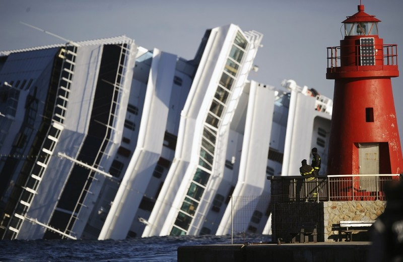 (FILES) This file photo taken on January 17, 2012 shows firemen looking at the emerged side of the cruise liner Costa Concordia on January 17, 2012. Disgraced Concordia captain Francesco Schettino awaits today on May 31, 2016 for the verdict of an appeal against the 16-year jail sentence he was handed last February for his part in the Costa Concordia shipwreck which killed 32 people.  Schettino was sentenced in February 2015 to 16 years and one month in jail after a judge ruled his recklessness caused the giant Costa Concordia to hit underwater rocks off the Tuscan island of Giglio. / AFP PHOTO / FILIPPO MONTEFORTE