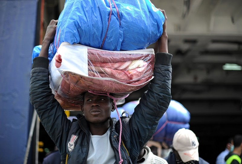 An African migrant carrying his belongings disembarks from the Red Star, chartered by the International Organisation for Migration (IOM) and carrying 800 migrants and civilian casualties from the besieged Libyan city Misrata, upon arrival in the rebel stronghold of Benghazi on May 5, 2011. AFP PHOTO / SAEED KHAN / AFP PHOTO / SAEED KHAN